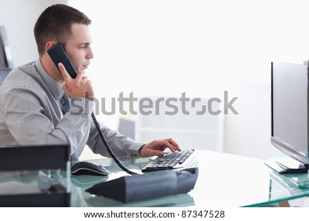 Young businessman typing while on the phone