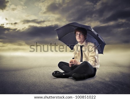 Young businessman under an umbrella with stormy sky in the background - stock photo