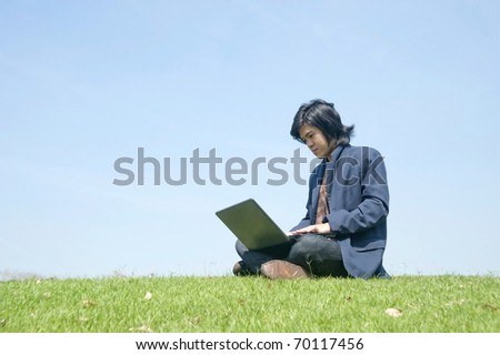 young businessman use a notebook on green field