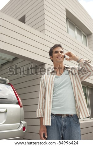 Young businessman using a cell phone at home, standing by his car. - stock photo
