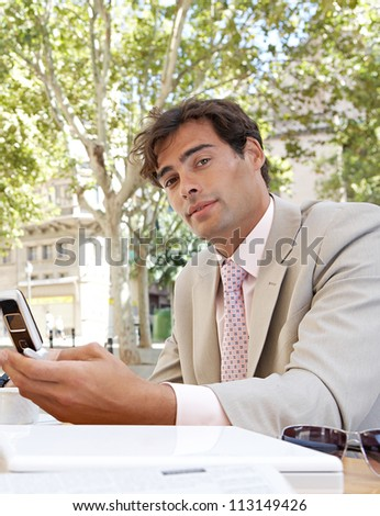 Young businessman using a cell phone while sitting in a coffee shop terrace table. - stock photo