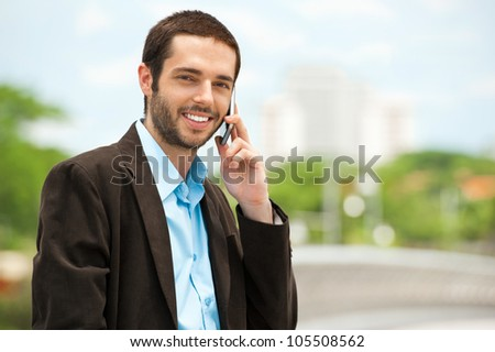 Young businessman using a mobile phone outdoors - stock photo