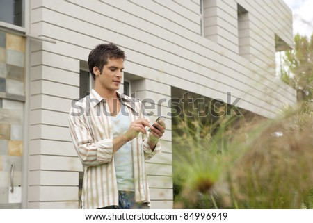 Young businessman using a smart cell phone near modern building. - stock photo