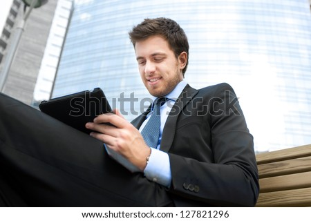 Young businessman using a tablet on a bench in the city - stock photo