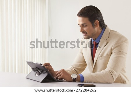 Young businessman using digital tablet at office desk