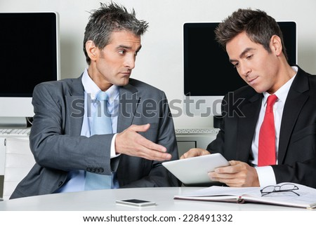 Young businessman using digital tablet while sitting with colleague at desk in office - stock photo