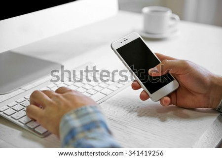 Young businessman using his phone and computer, close up - stock photo