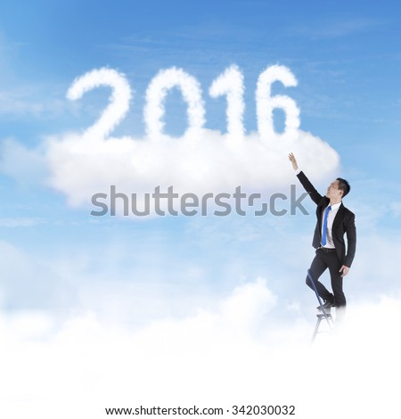 Young businessman using ladder to take clouds shaped numbers 2016 on the sky