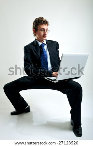 Young businessman using laptop in unusual position - stock photo