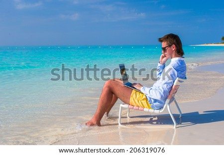 Young businessman using laptop on tropical beach