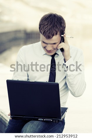 Young businessman using laptop outdoor - stock photo