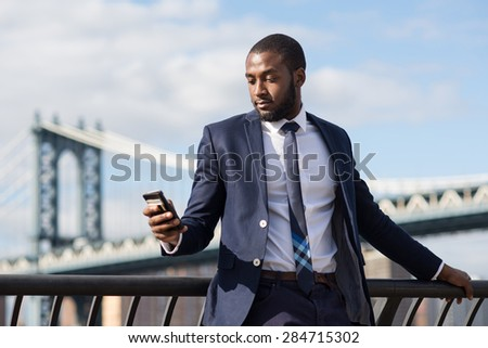 Young businessman using mobile phone phone with Manhattan Bridge in the background. Brooklyn Dumbo Park, New York City. - stock photo