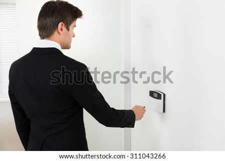 Young Businessman Using Remote Control For Operating Door Security System - stock photo