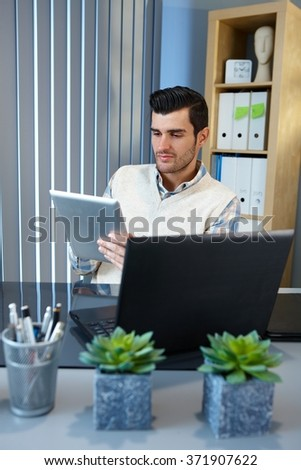 Young businessman using tablet computer, sitting at desk. - stock photo