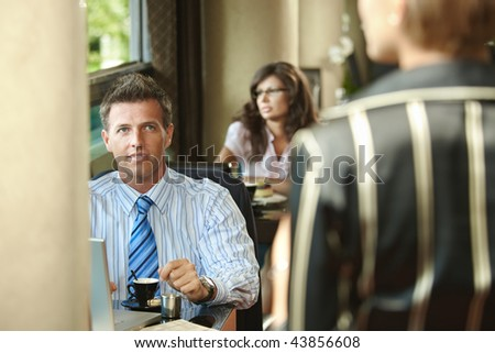 Young businessman waiting at cafe table drinking coffee,  businesswoman arriving for the meeting.