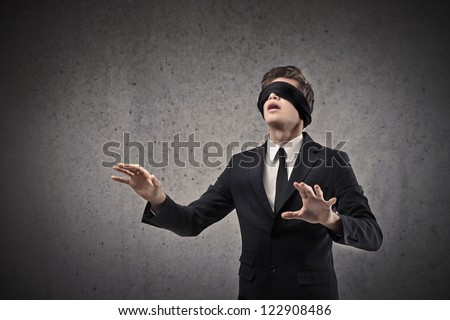 Young businessman walking blindfolded - stock photo