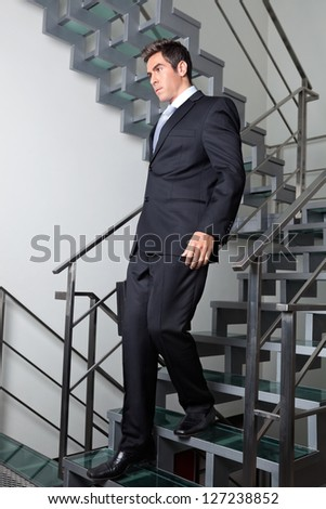 Young businessman walking down the stairs at office - stock photo