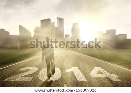 Young businessman walking for the future in the road - stock photo