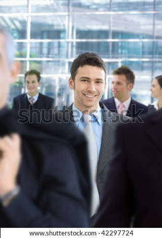Young businessman walking in crowd in office lobby, smiling.