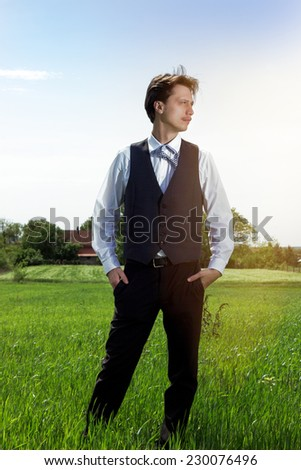 Young businessman walking in the nature, relaxing and thinking. Hands in pockets, selective focus, lens flare. - stock photo