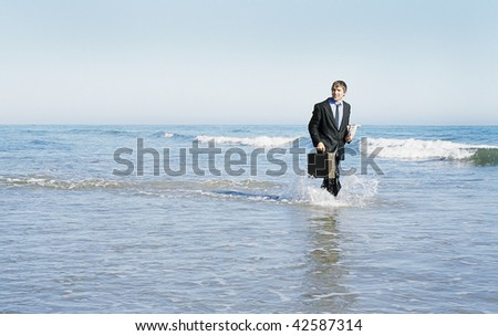 Young Businessman walking in the ocean in a suit.