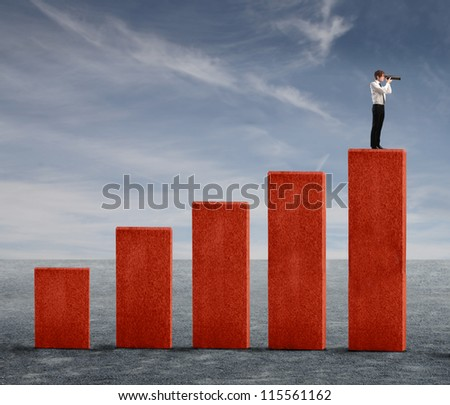 Young businessman watching into a telescope from the top of a business analysis - stock photo