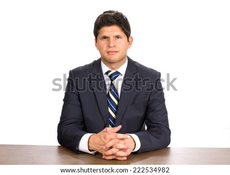 Young businessman wearing a pin stripe suit sits at a table with his hands interlaces. - stock photo