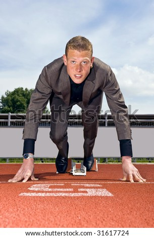 young businessman wearing a suit in the starting blocks to start building his career - stock photo