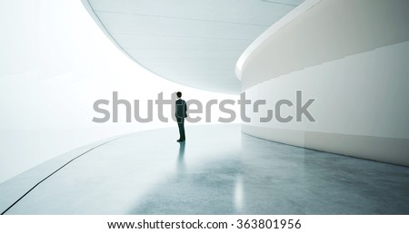 Young businessman wearing suit and stands in the open space interior. Wide - stock photo
