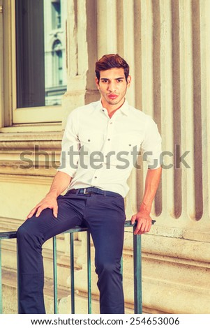 Young Businessman. Wearing white shirt, sleeves rolling over, black pants, a young college student sitting on a railing outside office, relaxing, thinking. Man Casual Fashion. Instagram filtered look. - stock photo