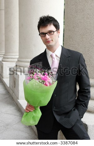 Young businessman with a bunch of flowers. - stock photo