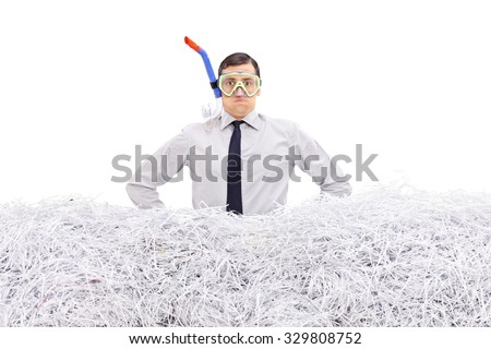 Young businessman with a diving mask standing in a pile of shredded paper isolated on white background - stock photo