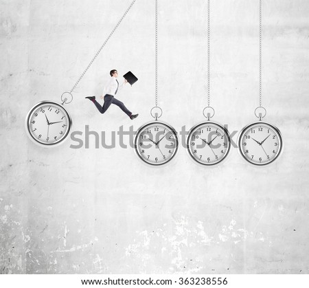 Young businessman with a folder in hand jumping from one hovering pocket watch to another, concrete background. Concept of coping with the task.