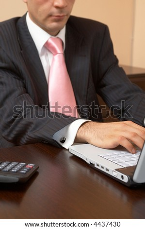 young businessman with a laptop and calculator at the office