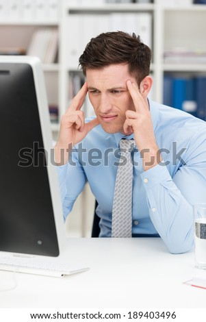 Young businessman with a problem at the office sitting at his desk with his hands to his temples frowning at his computer screen - stock photo