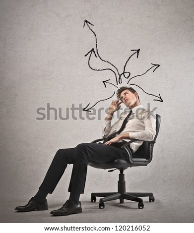 Young businessman with arrows in different directions on his head lying on a chair - stock photo