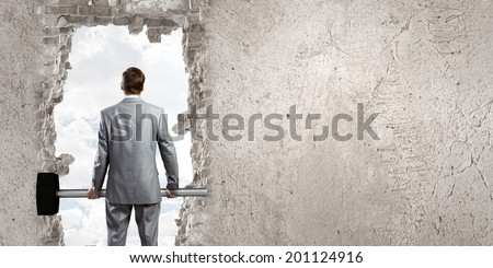 Young businessman with big hammer against wall - stock photo