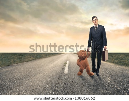young businessman with big teddy bear and briefcase on the road - stock photo