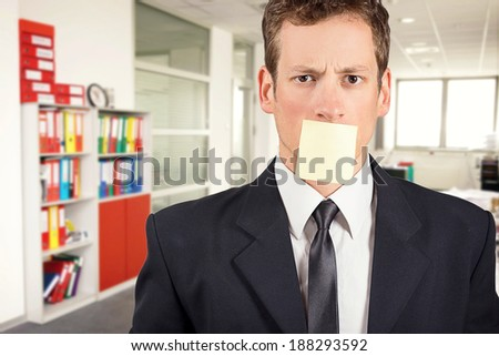 Young businessman with blank note on his mouth, inside office. - stock photo