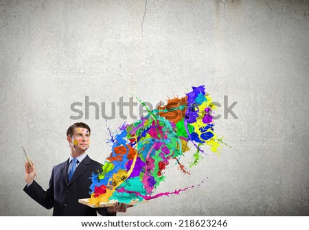Young businessman with brush in hand and colorful paint splashes