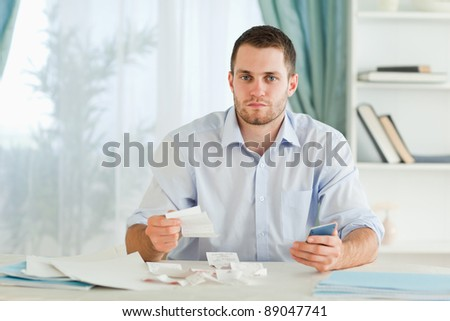 Young businessman with calculator checking invoices