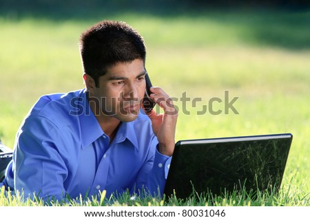 young businessman with cell phone and laptop at the park - stock photo