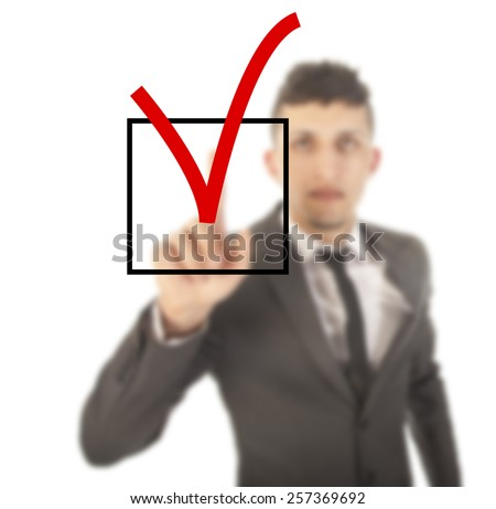 Young businessman with checkbox isolated on white background - stock photo