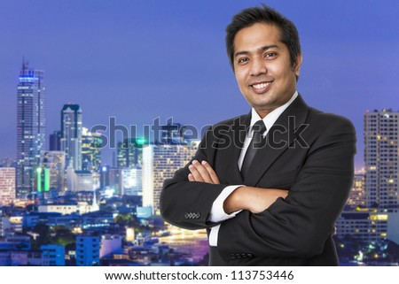 Young businessman  with cityscape in the background - stock photo