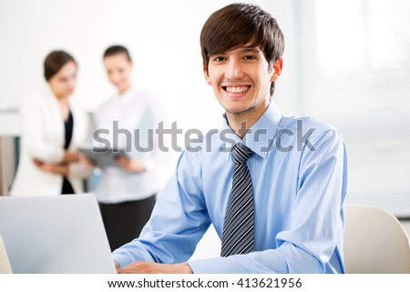 Young businessman with colleagues discussing in the background - stock photo