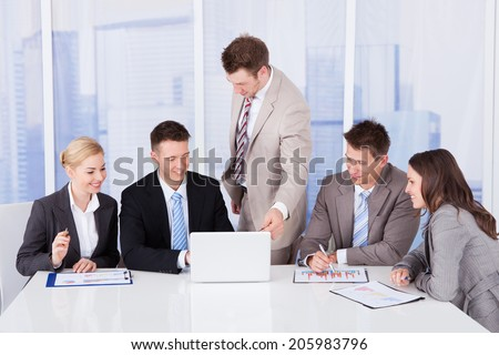 Young businessman with colleagues discussing on laptop in office - stock photo