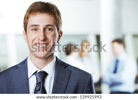 Young businessman with colleagues in the background - stock photo