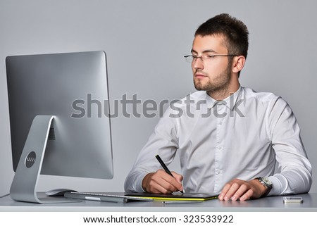 Young businessman  with computer taking notes, isolated on gray background.