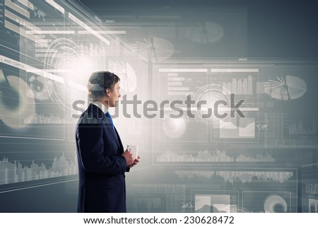 Young businessman with cup in hand looking at media screen - stock photo