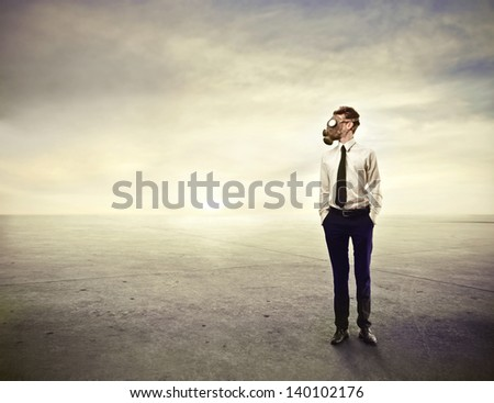 young businessman with gas mask in the desert - stock photo